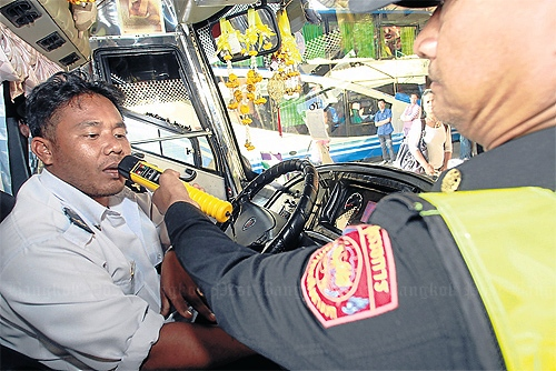 A Land Transport Department official conducts an alcohol test on an interprovincial bus driver at Mor Chit bus terminal.