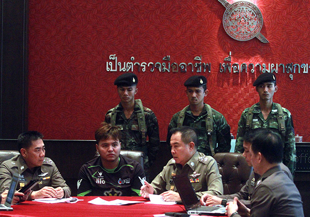 Krit Buddeejin, a 25-year-old musician from Phetchabun, is flanked by military officers at a press conference Wednesday. He is charged with allegedly disseminating a forged statement from the Royal Household Bureau about His Majesty the King's health. (Photo by Thanarak Khunton)