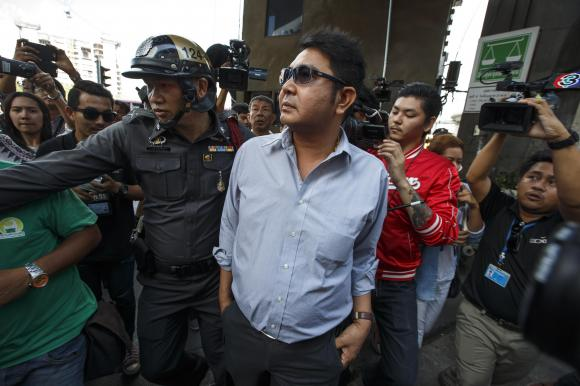 Thai pro-democracy protester Akkarakit Noonchan (C) is detained by a police officer near Victory Monument in Bangkok