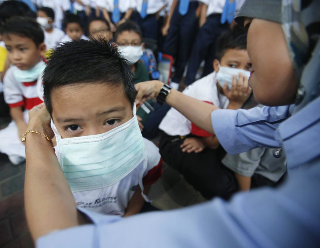 A teacher helps her student put on a face mask due to the haze
