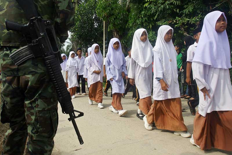 Thai Muslim school children walk past a soldier during a parade in the Takbai district of Thailand's restive southern province of Narathiwat