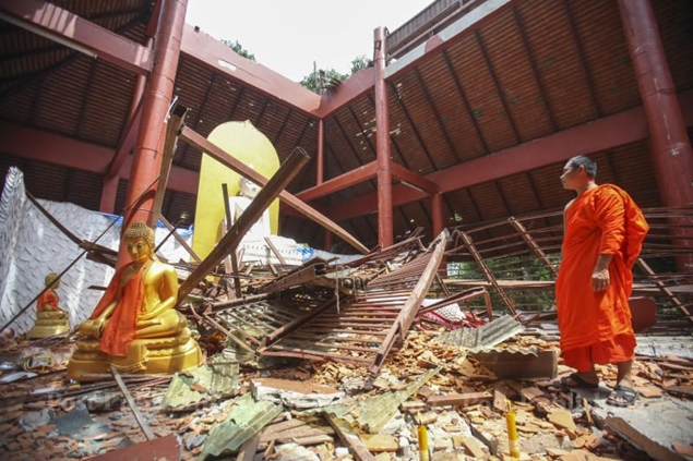 A monk surveys the damage to a prayer hall at Wat Mae Lao Woraram in Mae Lao district of Chiang