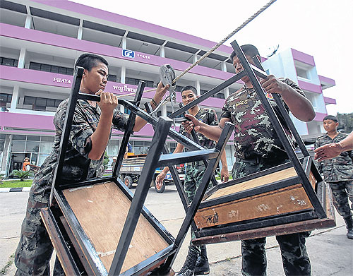 Soldiers move out tables from a building at Phan Pittayakom School in Chiang Rai after Quake