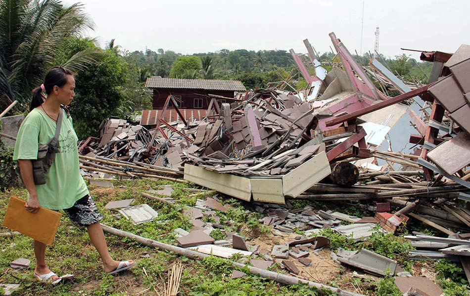 Thai woman Wallada Wiranondburapat, 34, looks at her collapsed house following an earthquake in Chiang Rai province