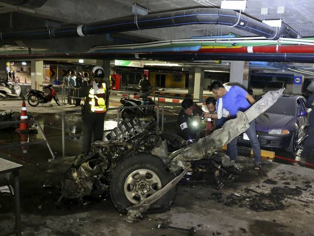 Police officers inspect the site of a car bomb blast at a car park of a shopping mall on the Thai tourist island of Koh Samui