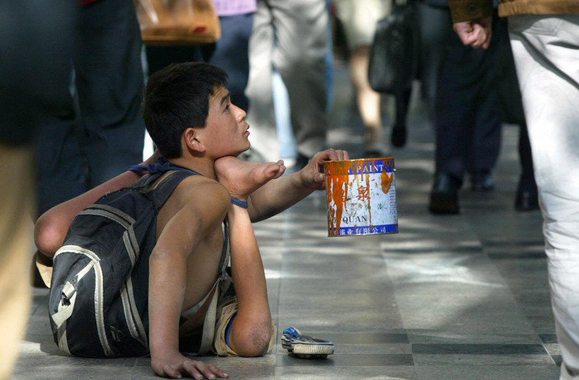 A disabled beggar begs for alms from pas