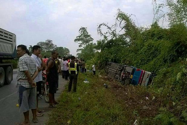 A police officer photographs the Phuket-bound bus that overturned in Plai Phraya district of Krabi on Saturday, injuring 25 passengers. (Photo: Facebook/Plodpai Samha)