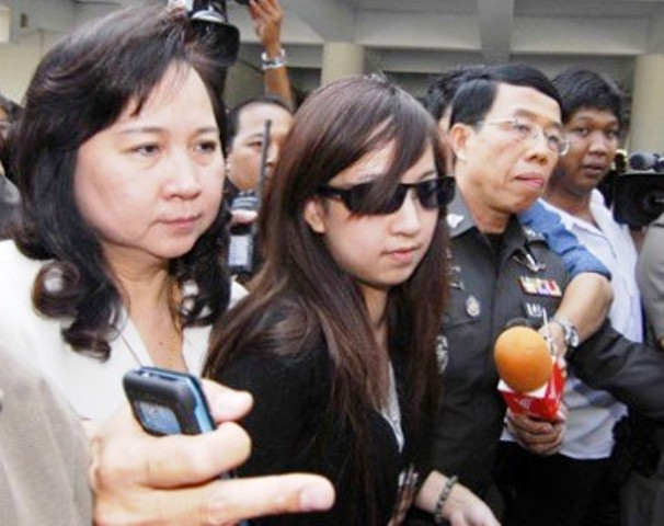 Orachorn (Praewa) Thephasadin Na Ayudhya, accompanied by mother and lawyer, emerges from the Metropolitan Police Headquarters