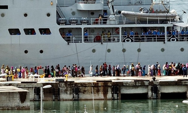 Rohingya migrants stand in a queue to board a Malaysian navy ship in Langkawi