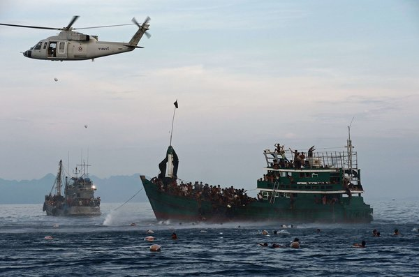 Rohingya migrants swam to collect food supplies dropped by a Thai army helicopter