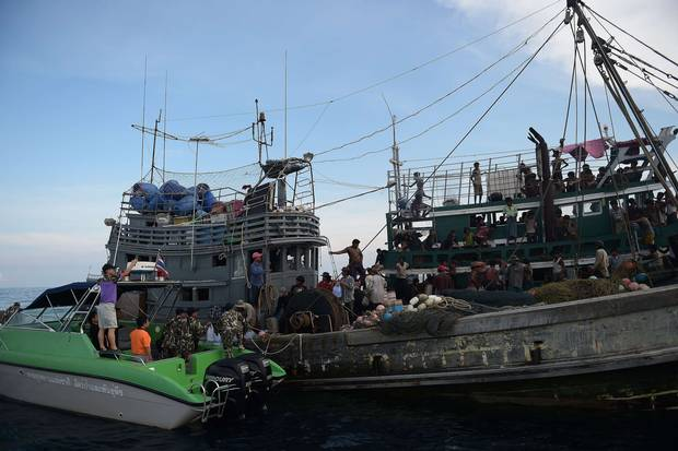 Fishermen (C) and National Park officials (L) provide food supplies to Rohingya migrants stranded on a boat (R) drifting in Thai waters off the southern island of Koh Lipe in the Andaman sea.