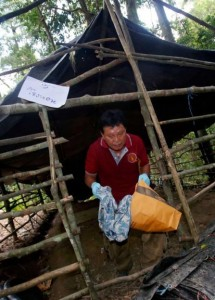 A forensic police officer collects items left at an abandoned migrant camp on Khao Kaew Mountain