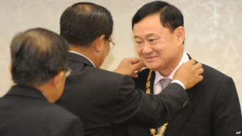 Former Thai Prime Minister Thaksin Shinawatra, right, receives a medal from Cambodia's Prime Minister