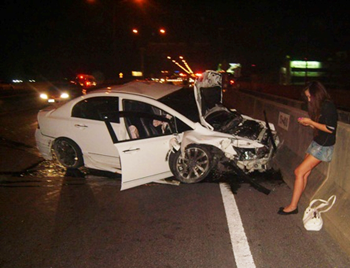 "Orachorn ""Praewa"" Thephasadin Na Ayudhya is seen toying with her smart phone right after her car crashed into the passenger van on the Don Muang expressway on Dec 27, 2010. (File Photos)"