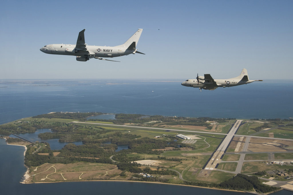 A P-8A Poseidon flying alongside a Lockheed P-3 Orion