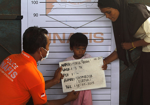 A Rohingya child who recently arrived by boat has his picture taken for identification purposes at a shelter in Kuala Langsa, in Indonesia