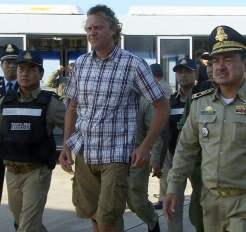 Russian Sergei Polonsky (centre) is escorted by Cambodian police at Phnom Penh international airport on May 17, 2015 - See more at: http://www.themalaymailonline.com/world/article/fugitive-russian-tycoon-sergei-polonsky-deported-out-of-cambodia#sthash.Ifi9xqlF.dpuf