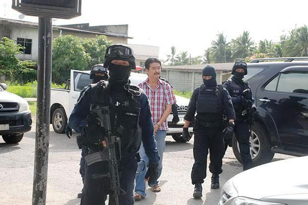 officers take Mr Banjong, who turned himself in to police on Friday, to search his house on May 9. Please credit and share this article with others using this link:http://www.bangkokpost.com/news/general/556235/alleged-trafficking-kingpin-properties-searched. View our policies at http://goo.gl/9HgTd and http://goo.gl/ou6Ip. � Post Publishing PCL. All rights reserved.