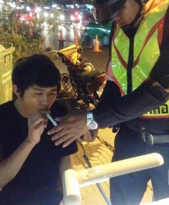 Policeman give breathalyzer test to Motorist