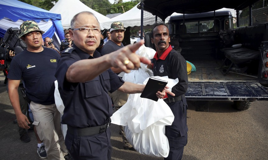 A forensic policeman transports body bags with human remains found at the site of human trafficking camps in the jungle close the Thailand border after bringing them to a police camp near Wang Kelian in northern Malaysia May 25, 2015.  REUTERS/Damir Sagolj