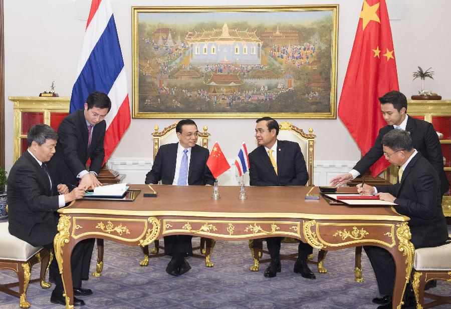 Chinese Premier Li Keqiang (center L) and Thai Prime Minister Prayuth Chan-ocha (center R) attend the signing ceremony of two memoranda of understanding on railway cooperation and farm produce trade cooperation respectively after they met in Bangkok