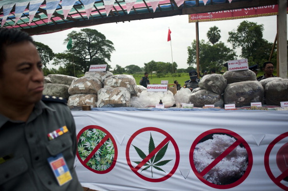 Myanmar police stand beside seized drugs before they are destroyed