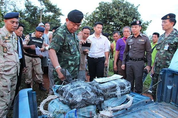 Authorities inspect speed pills wrapped in black plastic packs found in an abandoned pickup truck in Chiang Rai's Muang district on Wednesday evening. (Photo by Chinpat Chaimon)