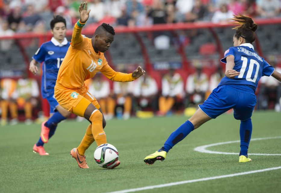 Ivory Coast's Binta Diakite dribbles past Thailand's Sunisa Srangthaisong during a Group B match at the 2015 FIFA Women's World Cup at Lansdowne Stadium in Ottawa