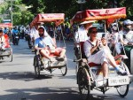 Foreign tourists enjoy a city tour by cyclos in downtown Hanoi
