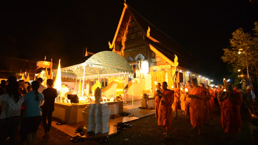 Asalha Puja Day, Buddhist monk walk with lighted candles in hand around a temple to the Buddha