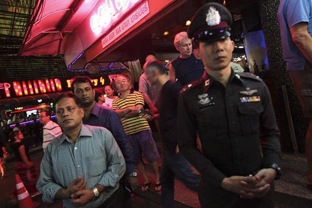 A police officer standing outside a bar in the Soi Cowboy nighttime entertainment area on Sukhumvit Road in Bangkok
