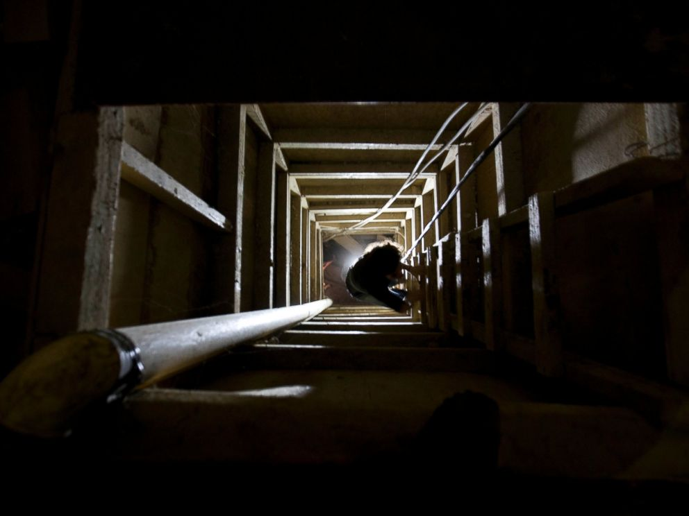 """A journalist climbs a ladder to get out of the tunnel that according to authorities, drug lord Joaquin """"El Chapo"""" Guzman used to escape from the Altiplano maximum security prison in Almoloya, west of Mexico City"""