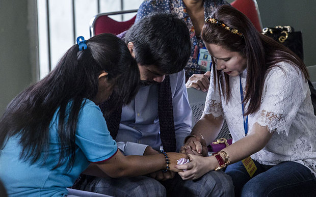 Manny Pacquiao (C) and his wife Jinkee (R), pray with convicted drug trafficker Mary Jane Veloso