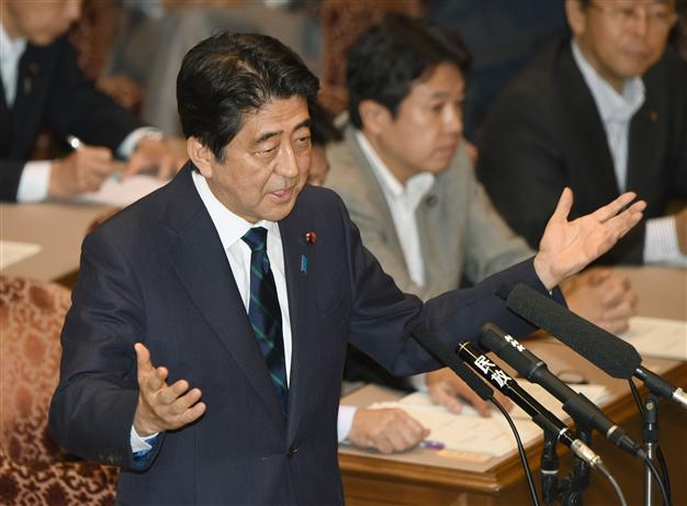 Japanese Prime Minister Shinzo Abe gestures as he answers questions from leader of the main opposition Democratic Party of Japan