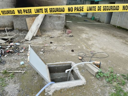 """Yellow tape around the house at the end of the tunnel through which Mexican drug lord Joaquin """"El Chapo"""" Guzman  escaped from the Altiplano prison"""
