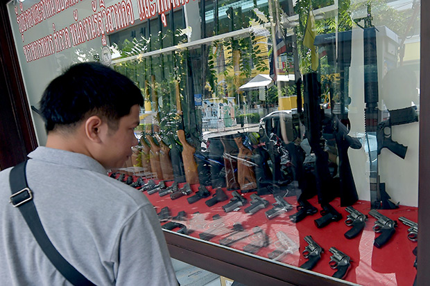 A Thai man looks at weapons displayed at a gun shop in Bangkok. Some 6.1 million firearms are registered in Thailand with its 67 million-strong population