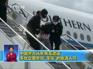 People being deported from Thailand are seen brought off an airplane by police at an unidentified location in China