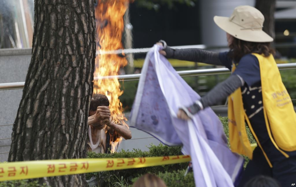 A South Korean man, left, sets himself on fire as a woman tries to extinguish him during an anti-Japan rally