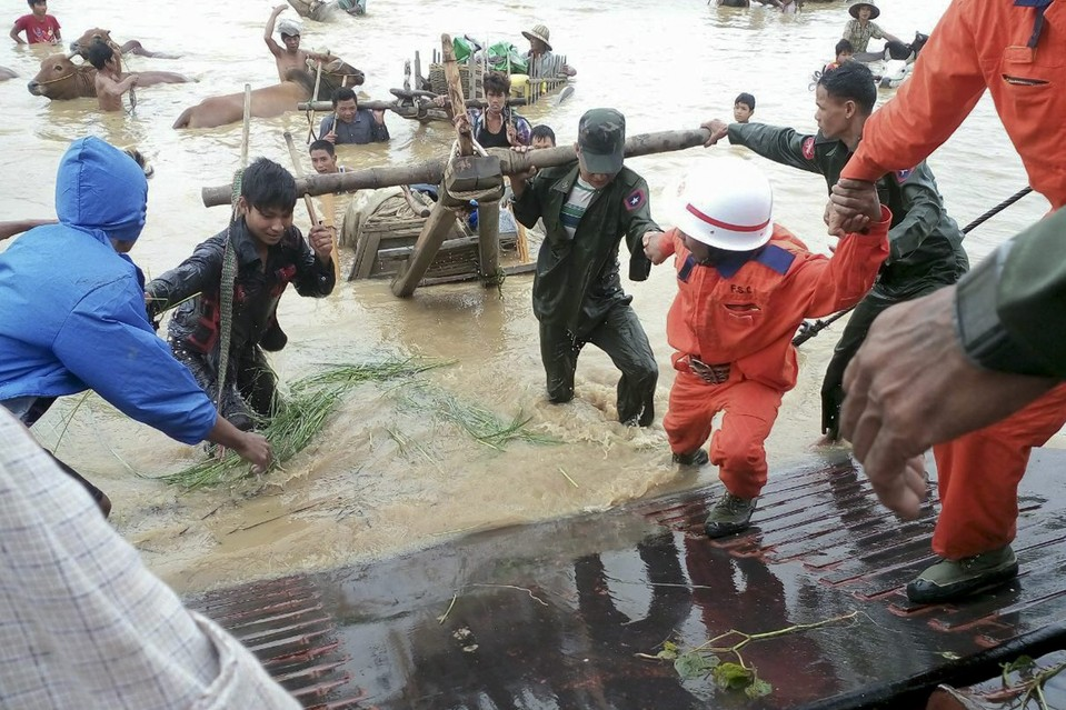 Rescue workers help humans and cattle out of a flooded area near Thayet township in Magway