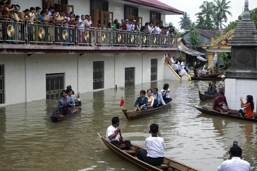 Myanmar opposition leader Aung San Suu Kyi riding in a boat, center, after visiting a monastery where flood victims are sheltered in Bago,
