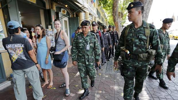 Military and police personnel walk past tourists as they patrol near the Grand Palace in Bangkok