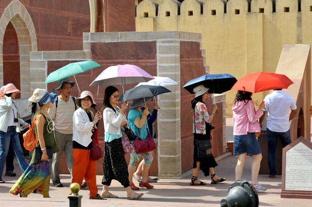 Tourists hold umbrellas as they visit