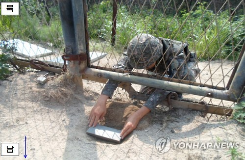 A South Korean soldier re-enacts burying a wooden-box mine around a gate on the southern side of the demilitarized zone (DMZ) near the city of Paju, north of Seoul