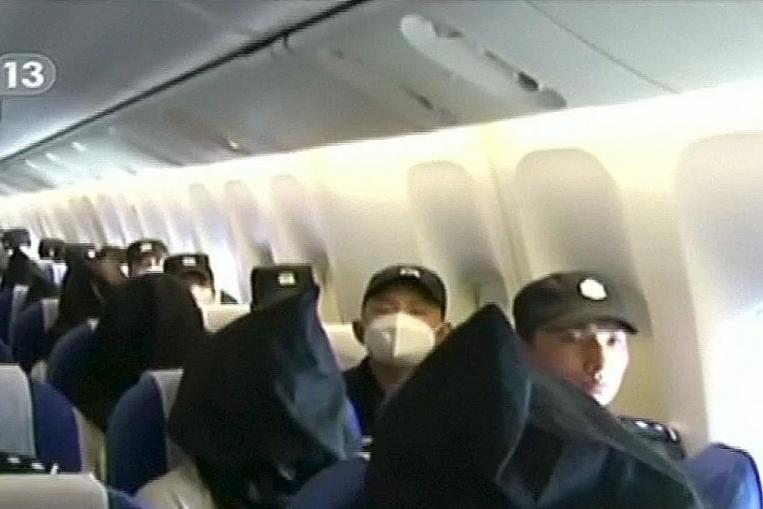 People being deported from Thailand seated in an airplane while flanked by police