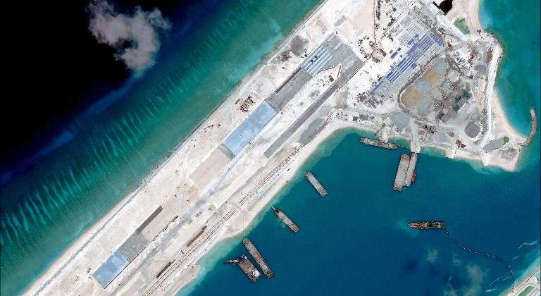China is rapidly building an airstrip on an artificial island in disputed South China Sea waters