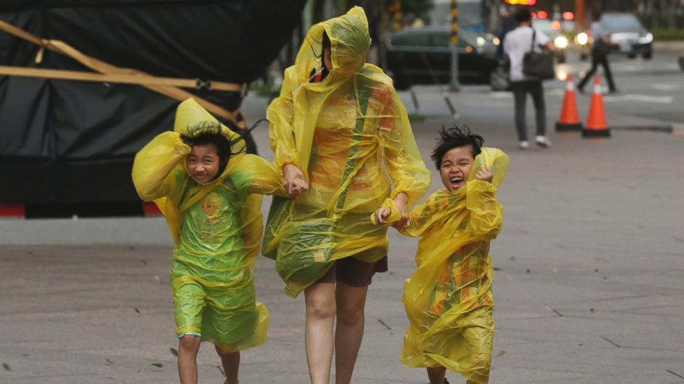A woman and children brave the strong winds from Typhoon Soudelor in Taipei
