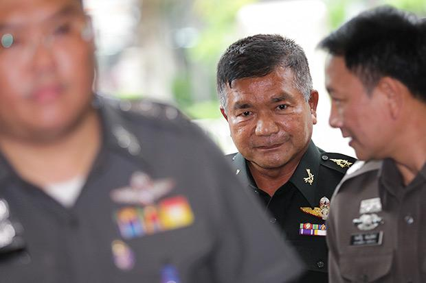 Senior army adviser Lt Gen Manas Kongpan is escorted June 4 by senior police officers for questioning as he turns up at the Royal Thai Police in Bangkok