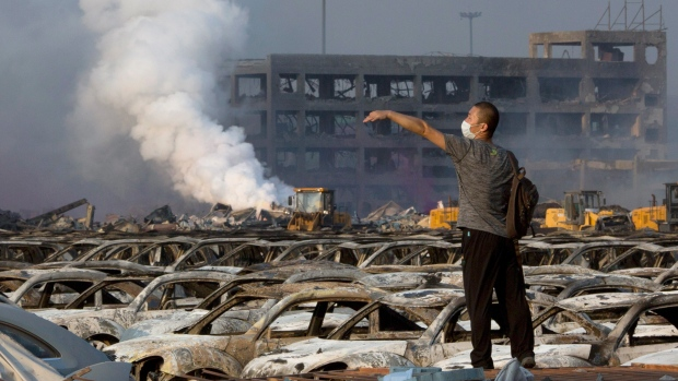A man walks on Thursday through the site of an explosion at a warehouse in northeastern China's Tianjin municipality