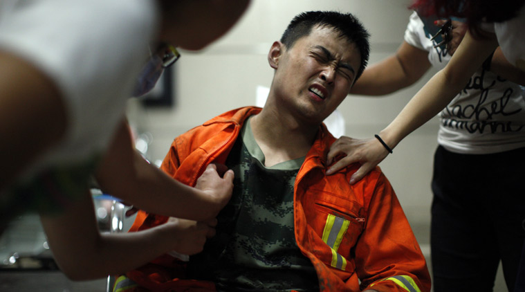 An injured firefighter grimaces as he is examined in a hospital following explosions in northeastern China's Tianjin