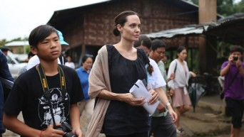 Actress Angelina Jolie Pitt, United Nations High Commissioner for Refugees special envoy, walks with her son Pax, left, as they visit Jan Mai Kaung refugee camp in Myitkyina, Kachin State, Myanmar, Thursday, July 30, 2015. (Hkun Lat/AP Photo)